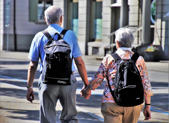 Zwei ältere Menschen mit Rucksäcken, die gegenseitig ihre Hand halten.